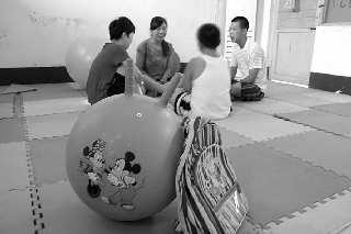 在市孤独症(智障)儿童康复中心,教师正给3个孩子做康复训练o(资料片)          摄图片