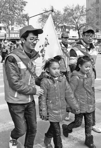 本报记者 李军 摄-志愿者小学门前 守护斑马线